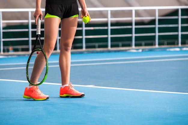ボールとラケットの閉じたテニスコートで若い女の子の足 無料写真