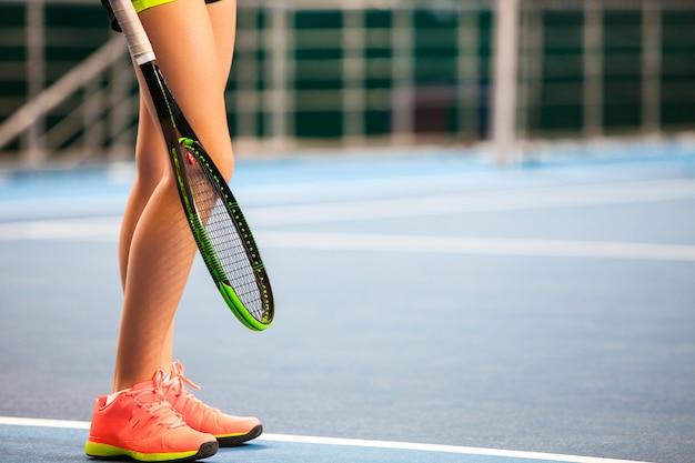Ноги молодой девушки в закрытом теннисном корте с ракеткой Бесплатные Фотографии