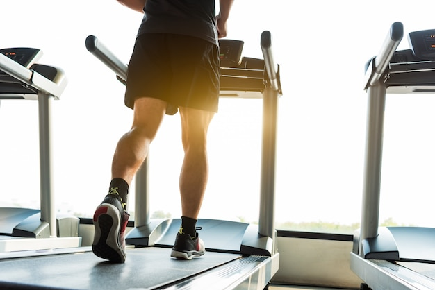 Legs of sportsman running on treadmill in fitness gym center. sport and healthy lifestyle concept. Premium Photo