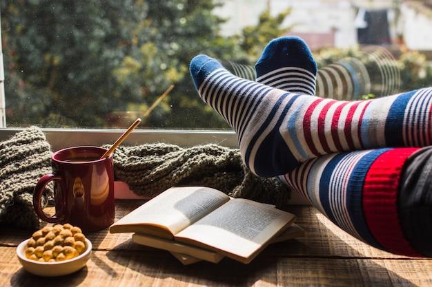 Legs in striped socks near window Free Photo
