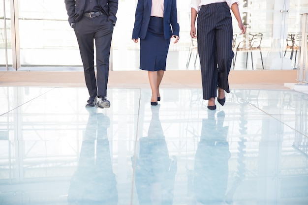 Legs of three business partners walking in office Free Photo