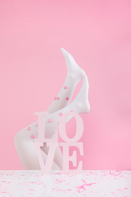 Legs in tights with paper hearts near white love inscription Free Photo