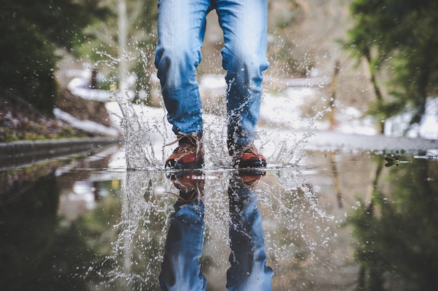 Legs wearing blue jeans and brown boots walking on the wet street Free Photo