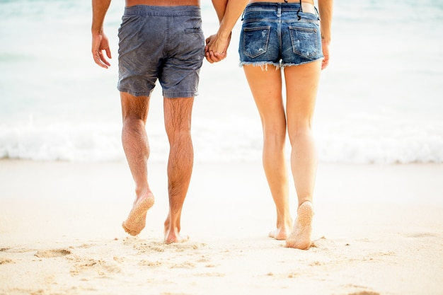 Legs of young couple walking on sand at seaside Premium Photo