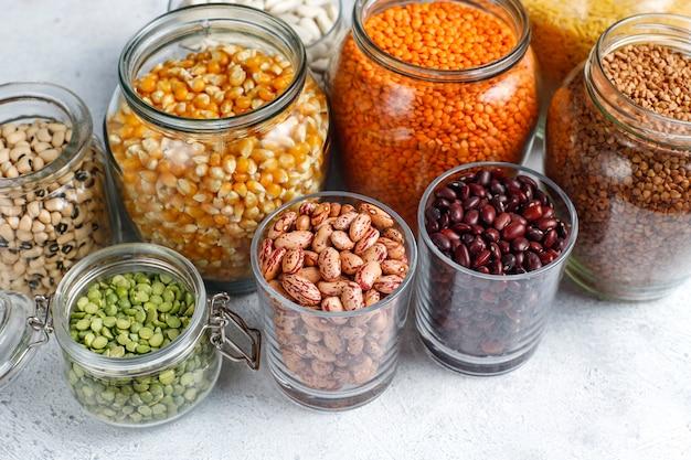 軽い石の背景に別のボウルにマメ科植物と豆の品揃え。上面図。健康なビーガンタンパク質食品。 無料写真