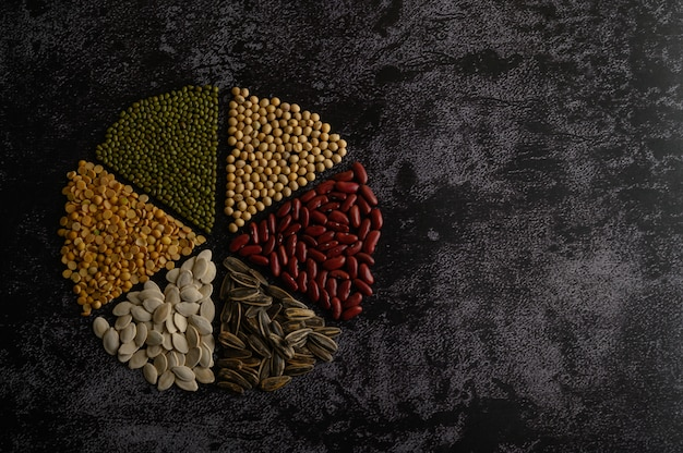 Legumes arranged in a circle on the black cement floor. Free Photo