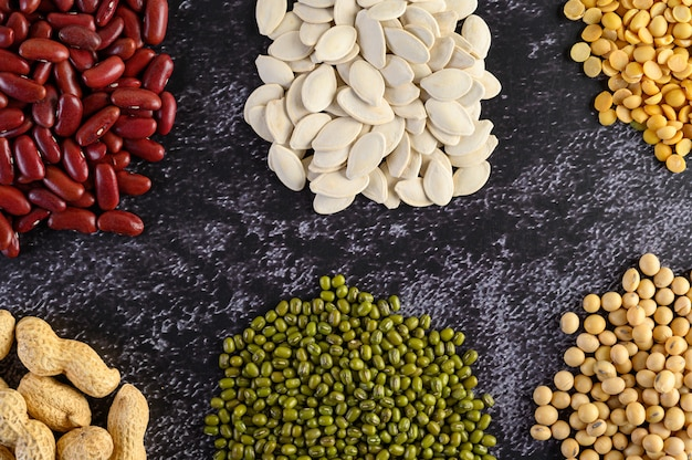 Legumes, and beans assortment on the black cement floor. Free Photo