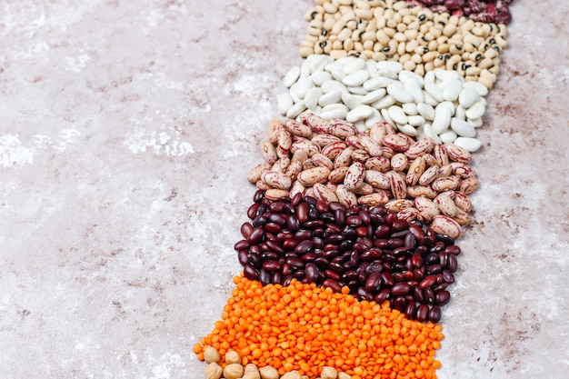 Legumes and beans assortment in different bowls on light stone background . top view. healthy vegan protein food. Free Photo