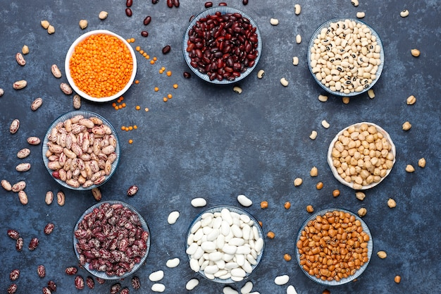 Legumes and beans assortment in different bowls on light stone surface . top view. healthy vegan protein food. Free Photo