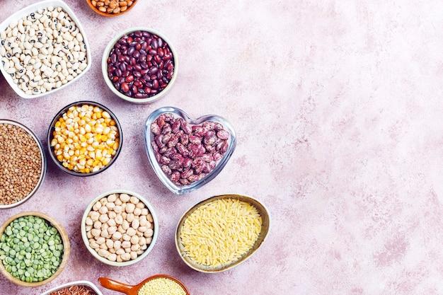 Assortimento di legumi e fagioli in diverse ciotole su pietra chiara. vista dall'alto. cibo proteico vegano sano. Foto Gratuite
