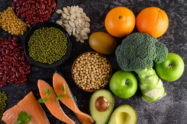 Legumes, broccoli, fruit, and salmon placed on a black cement floor. Free Photo