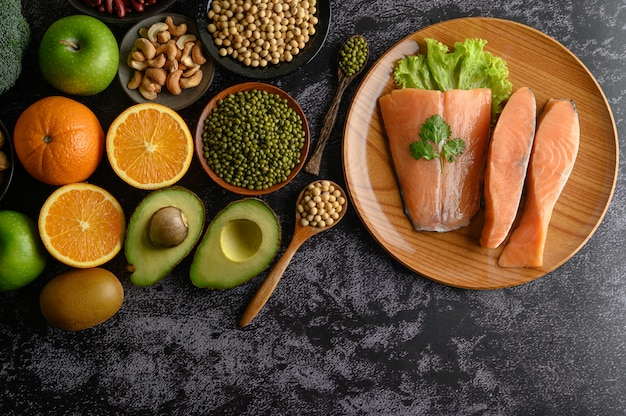 Legumes, fruit and salmon pieces on a wooden plate. Free Photo