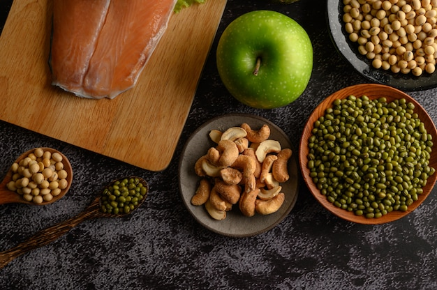 Legumes, salmon pieces and apple on a black cement floor surface. Free Photo