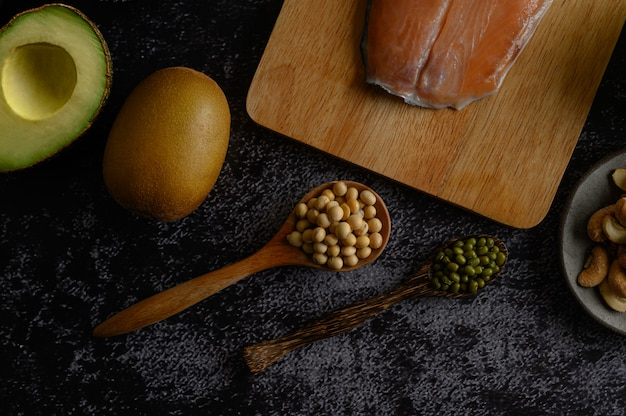 Legumes, salmon pieces and kiwi on a black cement floor surface. Free Photo