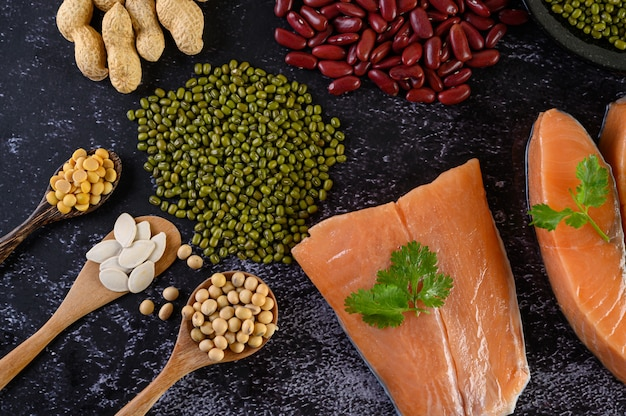 Legumes and salmon placed on a black cement floor. Free Photo