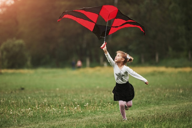 Leisure activity. happy girl in casual clothes running with kite in the field. beautiful nature Premium Photo