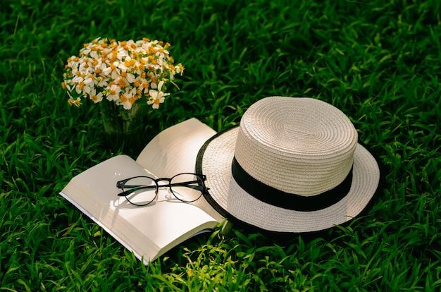 Отдых в саду с книгой, соломенной шляпой и цветами на лужайке. Premium Фотографии