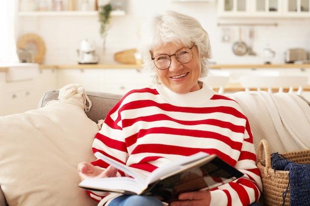 Tempo libero, auto educazione, hobby e concetto di pensionamento. immagine di bella femmina senior matura in maglione a righe e occhiali alla moda che gode della lettura in soggiorno, sorridendo con gioia Foto Gratuite