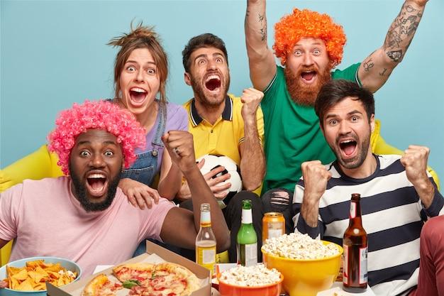 レジャー、スポーツ、幸福の概念。感情的な幸せな友達が手を挙げ、大声で叫び、ゴールを祝い、人気のあるサッカーチームの勝利を喜んで、軽食をとり、アルコール飲料を飲み、屋内でポーズをとる 無料写真
