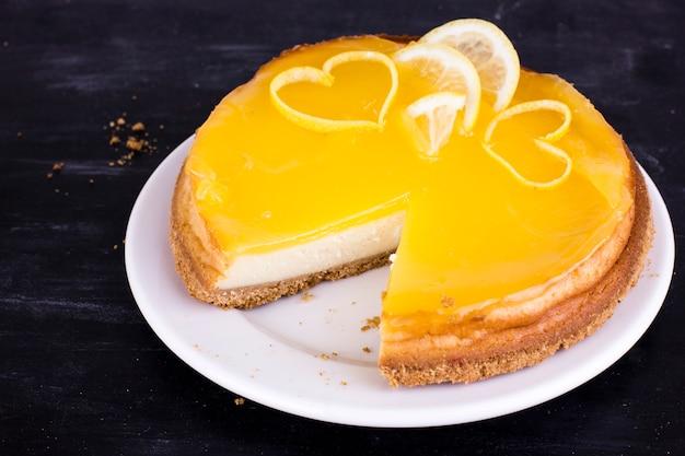 Lemon cheesecake on black background decorated with lemon zest close up Premium Photo