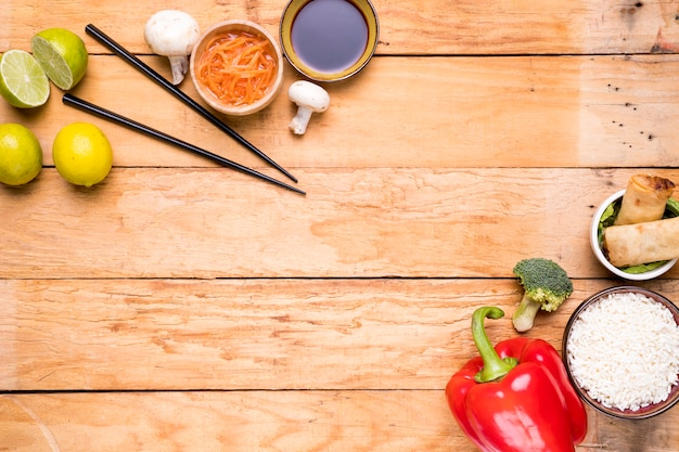 Lemon; chopsticks; mushroom; sauces; bell peppers; broccoli; rice and spring rolls on wooden plank Free Photo