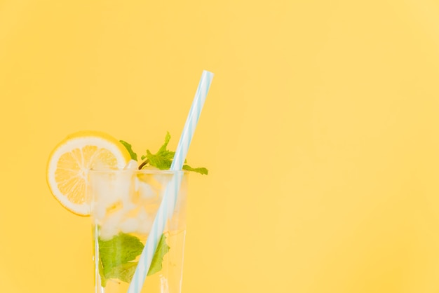 Lemon cocktail with plastic straw on yellow background Free Photo