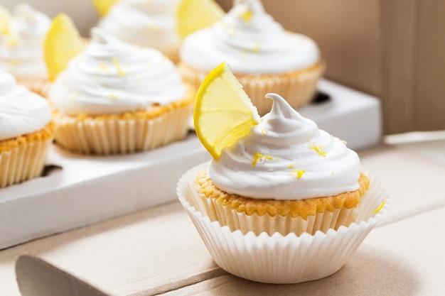 Лимонные капкейки с белым кремом в доставочной коробке Premium Фотографии