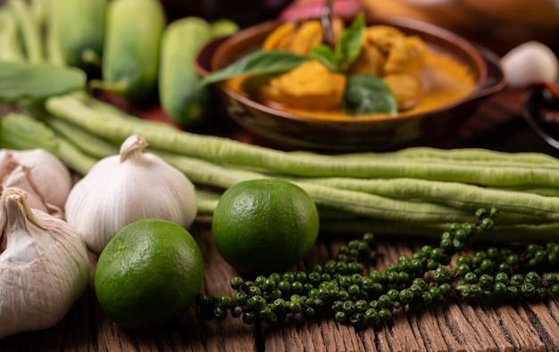 Limone, aglio, fagioli lunghi e semi di pepe fresco su un tavolo di legno Foto Gratuite