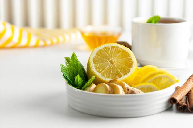 Lemon and ginger slices with mint white background Premium Photo