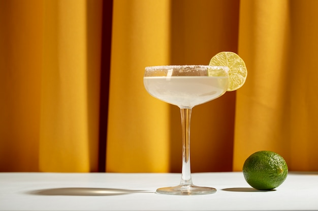 A lemon margarita cocktail with wedges of lime and salt on white table against yellow curtain Free Photo