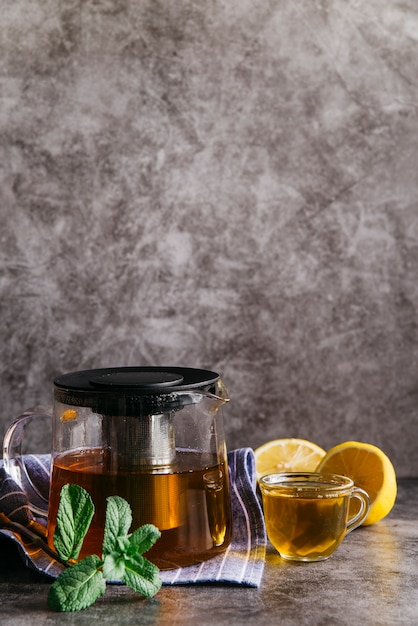 Lemon and mint herbal tea in transparent glass cup and teapot Free Photo