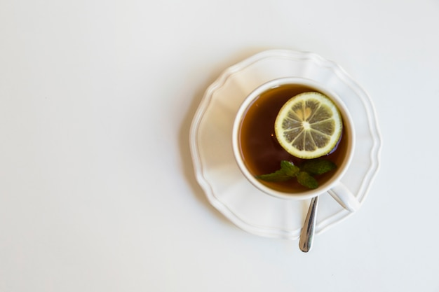 Lemon and mint tea cup; spoon on ceramic saucer over white background Free Photo