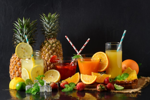 Lemon, orange and strawberry juice on black Premium Photo