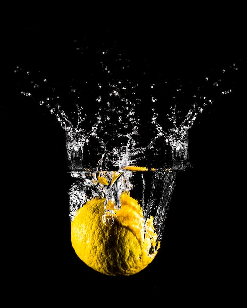 Lemon plunging into the water Free Photo