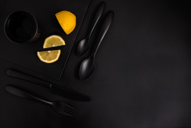 Lemon slices on a black background with black cutlery, a black glass and a black plate, top view Premium Photo