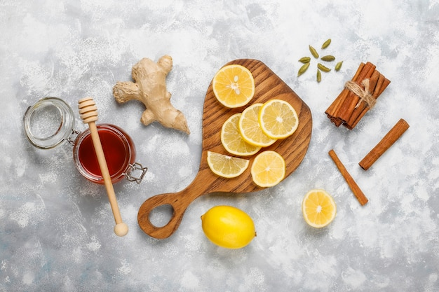 Lemon slices on cutting board,cinnamon sticks,honey on concrete  . top view, copy space Free Photo