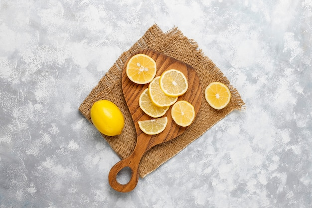 Lemon slices on cutting cutting board on concrete  . top view, copy space Free Photo
