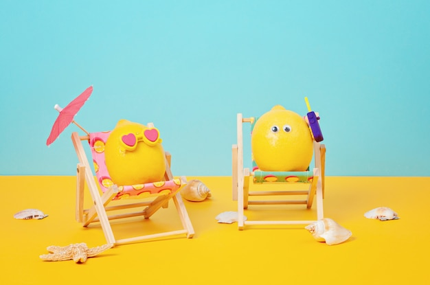 Lemon in sunglasses in the sunbed with umbrela at the beach Premium Photo