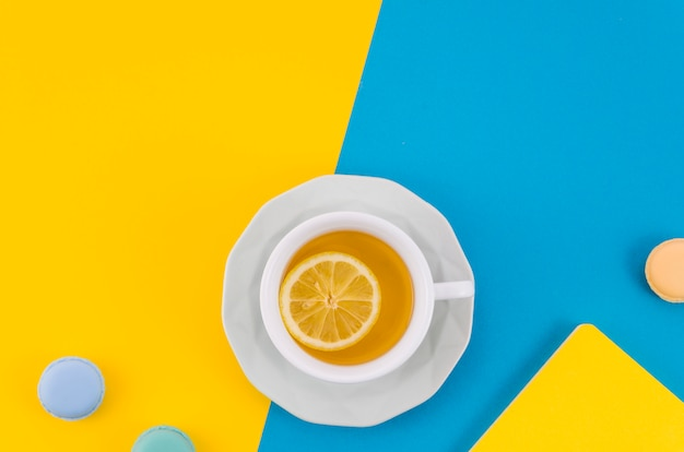 Lemon tea cup with macaroons on yellow and blue dual backdrop Free Photo