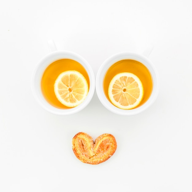 Lemon tea cups with palmiers pastry on white background Free Photo