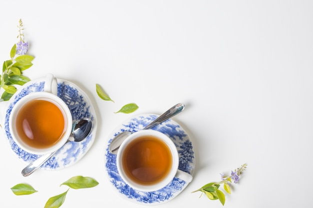 Lemon tea herbal leaves with cup and saucer against white backdrop Free Photo