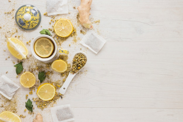 Lemon tea with dried chinese chrysanthemum flowers and lemon slices on wooden table Free Photo