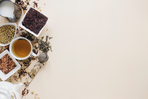 Lemon tea with dry tea leaves; dried chinese chrysanthemum flowers; tea strainer; milk; herbs and teapot on colored background Free Photo