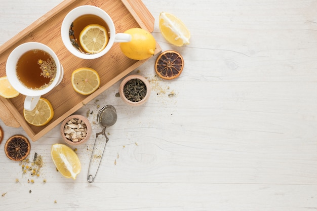 Lemon tea with lemons in tray and herbs on white wooden table Free Photo