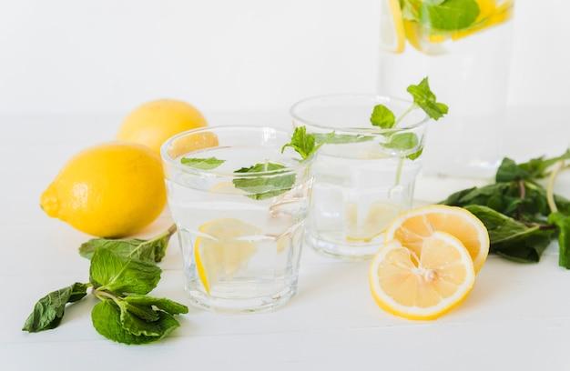 Lemon water in glasses and ingredients Free Photo
