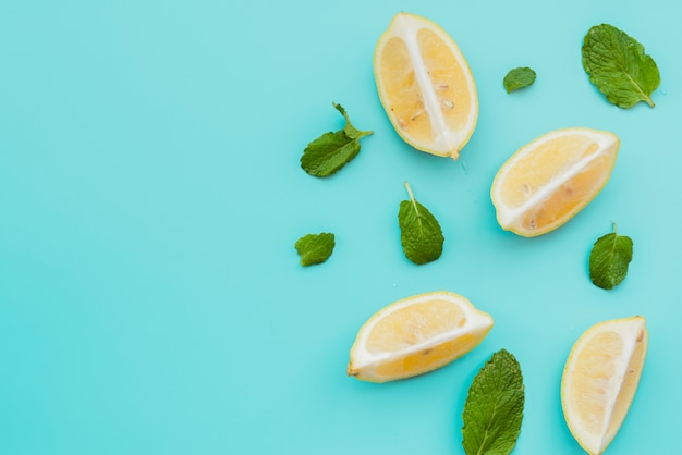 Lemon wedges and mint leaves on background Free Photo