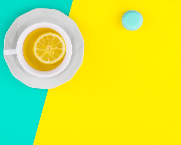 Lemon white tea cup and saucer with macaroon on turquoise and yellow backdrop Free Photo