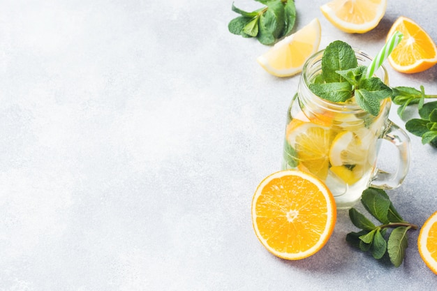 Lemonade drink of soda water, lemon and mint leaves in jar on light background Premium Photo