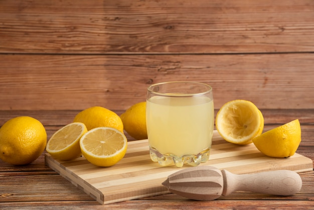 Lemonade in a glass cup on the wooden board Free Photo