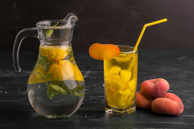 Limonata in vetro e vaso con pesche intorno isolato sulla superficie nera Foto Gratuite